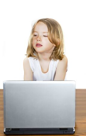 techie: Cute thinking child looking busy on laptop