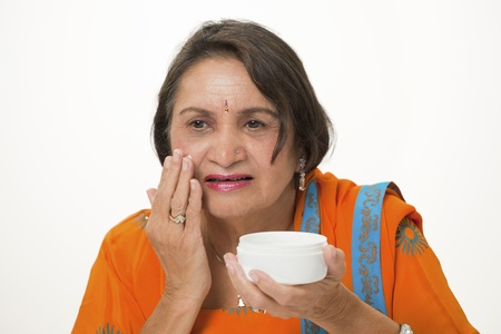 Mature woman applying anti-wrinkle face cream photo