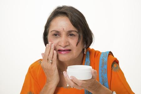 kameez: Mature woman applying anti-wrinkle face cream Stock Photo