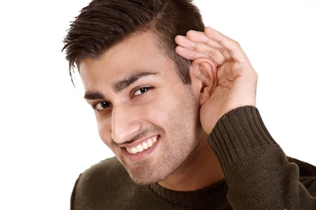 Listening man cupping ear with amused smile photo