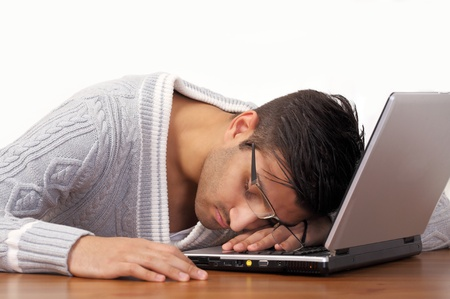 Tired guy sleeping on laptop photo