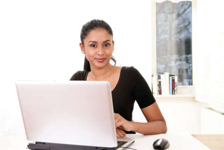 Sweet girl sitting at work-desk with laptop Stock Photo - 12082801