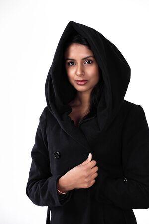 Beautiful ethnic woman in hood with black coat photo