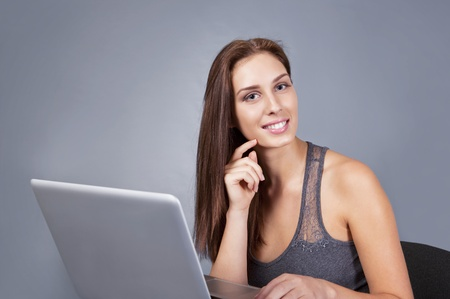 Smiling young woman with laptop looking up photo