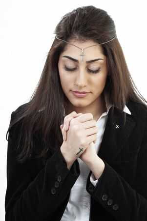 Devout young woman praying with holy cross photo