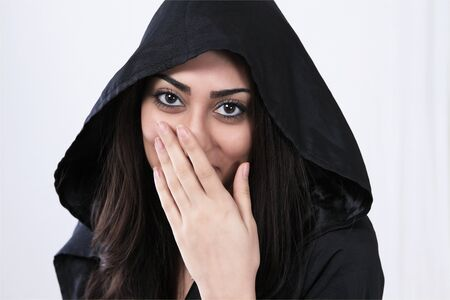 Laughing asian woman with hand covering face photo
