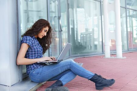 Pretty girl busy on laptop outside office building photo