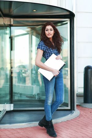 Smart young woman leaving an office building photo