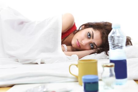 bedsheets: Sick girl in bed medicines and fluids in foreground Stock Photo