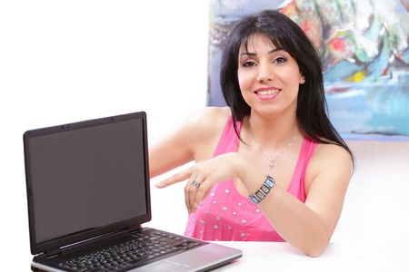 Beautiful smiling woman pointing at computer screen Stock Photo - 12908522