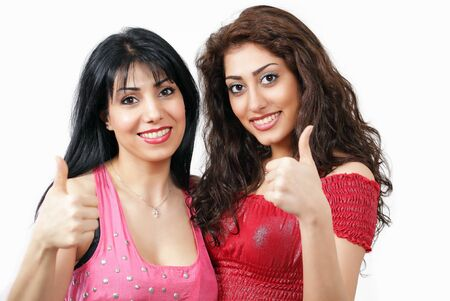 Thumbs up - two lovely smiling latino women photo
