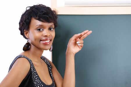 Smiling school teacher pointing to blackboard Stock Photo - 13111028