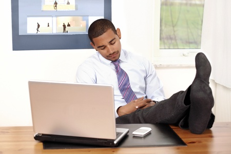 Man sleeping in office with feet on desk photo