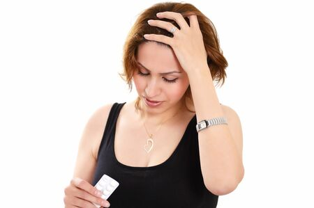 Pretty woman with severe migraine holding pills photo