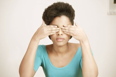 Young woman closing eyes with hands Stock Photo