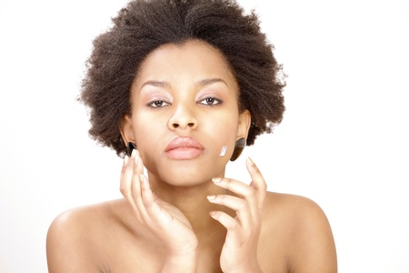 Lovely ethnic woman applying face cream or moisturizer photo