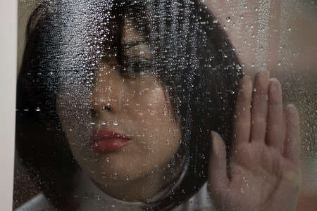 inclement: Woman at rainy window in dark rough weather Stock Photo