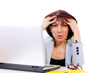 Confused office lady holding head sitting at computer