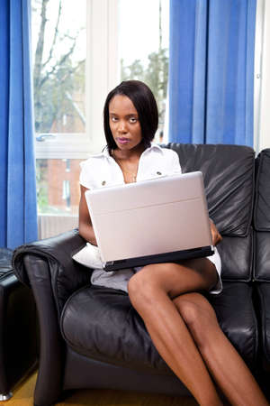 Beautiful young woman with laptop online at home photo