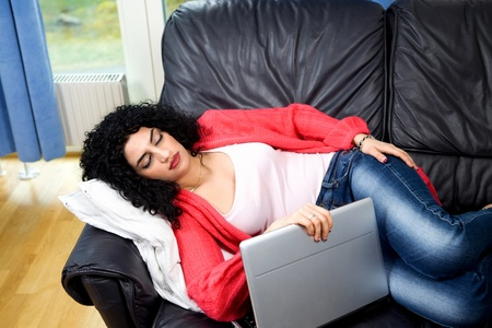 Sleeping woman holding laptop lying on sofa photo