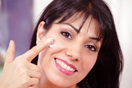 Smiling adult female applying face moisturizer photo