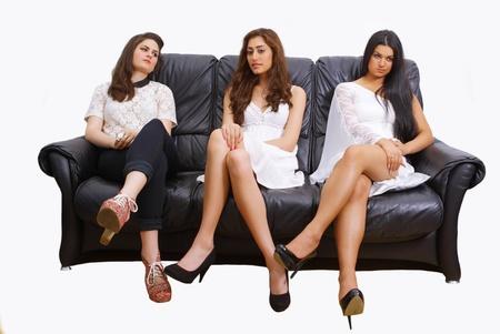 Three pretty women sitting on a sofa