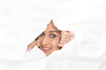peeping: Smiling woman peeping through a hole in paper Stock Photo