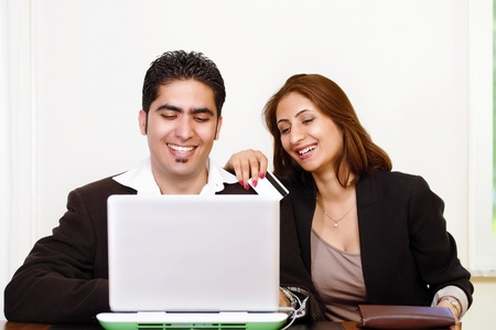 Happy couple shopping online with credit card photo