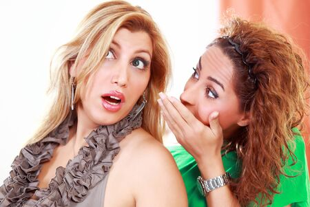 Gossiping women whispering and looking shocked photo