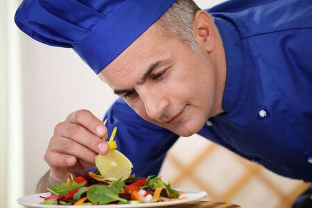 garnishing: Chef garnishing salad dish with care and attention Stock Photo