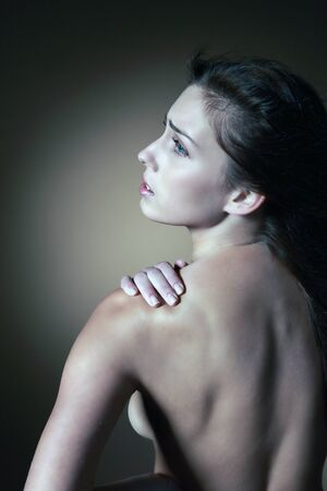 nude back: Backache, pretty woman holding upper back