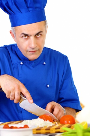 Chef in commercial kitchen chopping vegetables photo