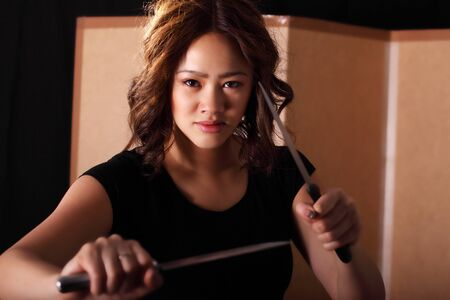 Tough martial arts girl with knives photo