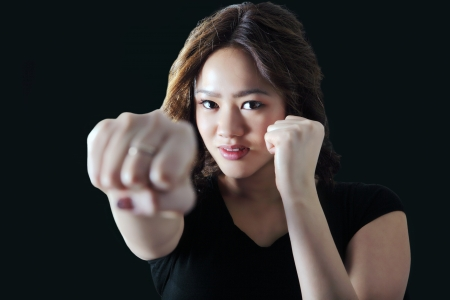 punching: Young woman practicing self defense throws a punch Stock Photo
