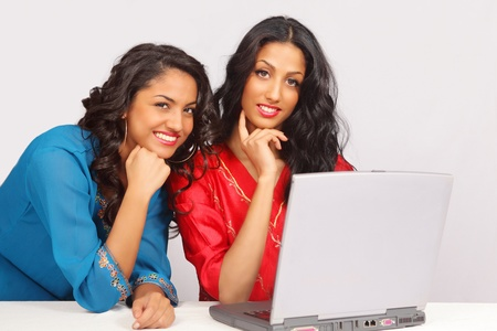 Cute smiling female students on laptop photo