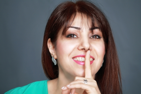 the color of silence: Smiling woman with finger on lips