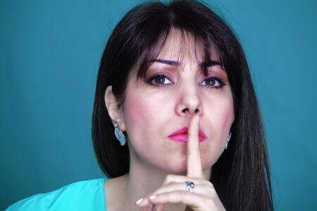 strict: Be silent! Strict school teacher with finger on lips Stock Photo