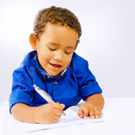 Cute kid writing or doodling with pen on paper