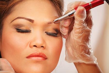 cejas: Tatuaje de la ceja del maquillaje, el joven asi�tico cara de la mujer