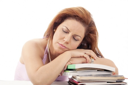 Tired woman asleep on pile of books photo