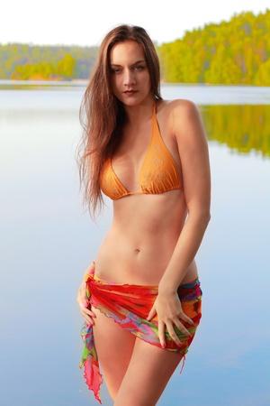 desirable: Pretty woman in bikini by lake at sunset