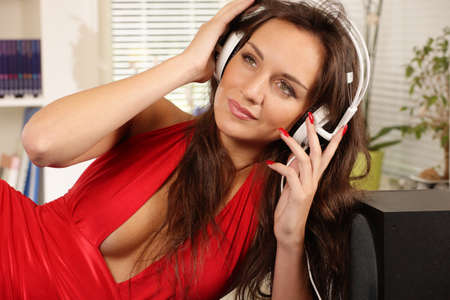 Listening to music, girl on headset in cluttered room Stock Photo - 21976796