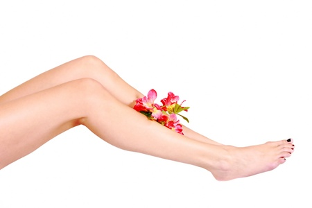 Womans legs after depilation, with sprig of flowers photo