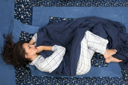 Woman sleeping in curled position, comfort in bed photo