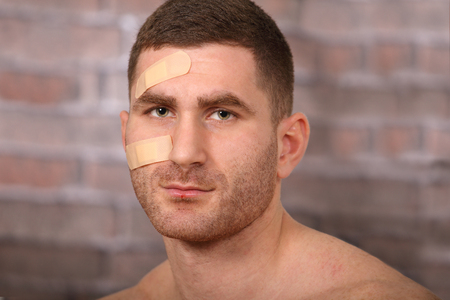 Man with plaster and bruises, after a fight photo