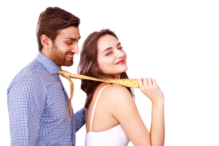 Leading him on by his tie, smiling playful couple Stock Photo