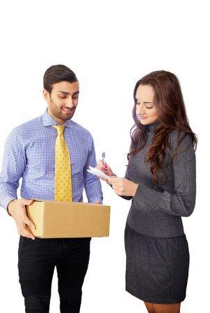 20 s: Woman signing for courier, delivery man in background Stock Photo