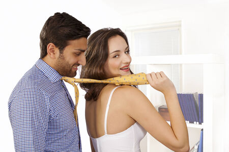 dominating:  Woman in control leading man by tie with smile