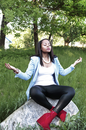 meditates: Stylish woman meditates in green nature Stock Photo