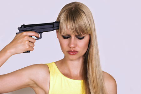 Woman puts gun to head with depressed look photo